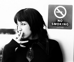 The Rebel: a girl smoking in front of a no-smoking sign